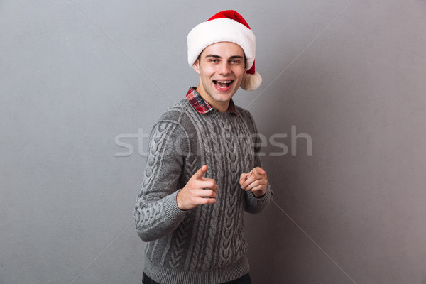 Happy man in sweater and christmas hat pointing at camera Stock photo © deandrobot