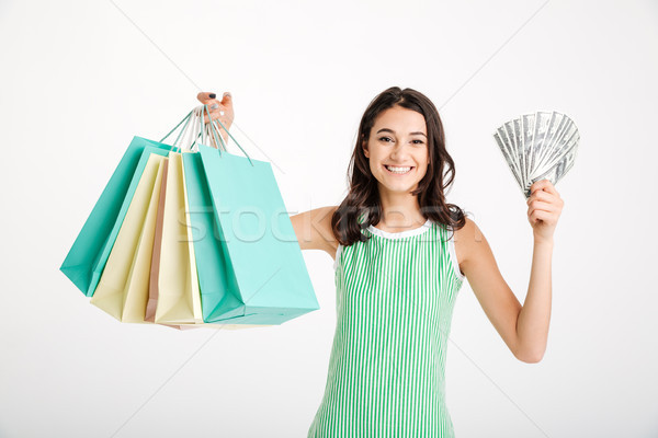 Portrait of a satisfied girl in dress holding shopping bags Stock photo © deandrobot