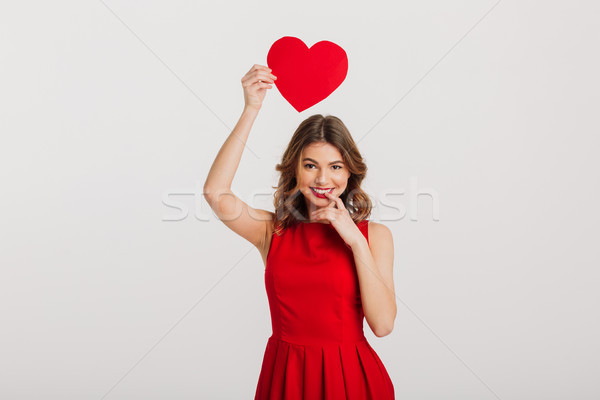 Portrait of a happy young woman dressed in red dress Stock photo © deandrobot