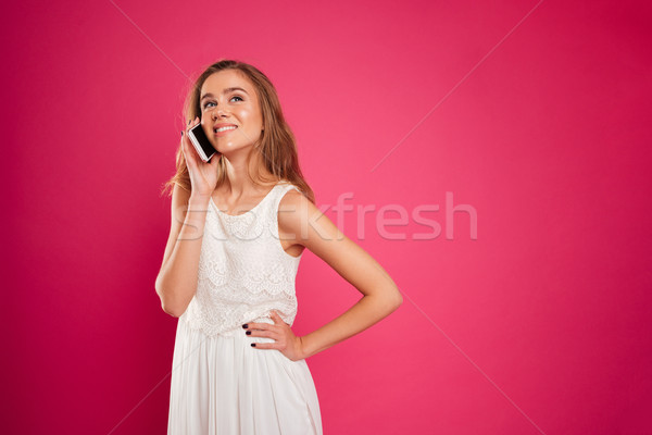 Portrait of a smiling pretty girl in dress talking Stock photo © deandrobot