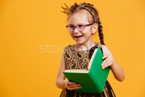 Pretty girl child wearing princess crown reading book. Stock photo © deandrobot