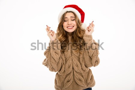 Surprised young lady dressed in warm sweater pointing to copyspace. Stock photo © deandrobot