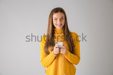 Happy brunette woman in sweater writing message on smartphone Stock photo © deandrobot