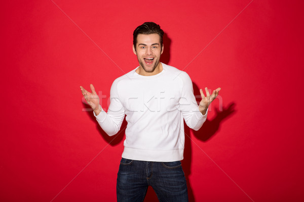 Image of Surprised cheerful man in sweater looking at camera Stock photo © deandrobot