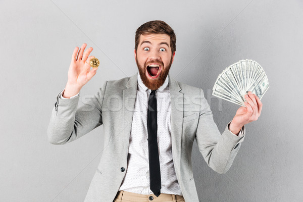 Portrait of an excited businessman showing bitcoin Stock photo © deandrobot
