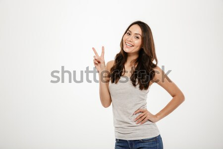 Smiling brunette woman with arm on hip showing peace gesture Stock photo © deandrobot