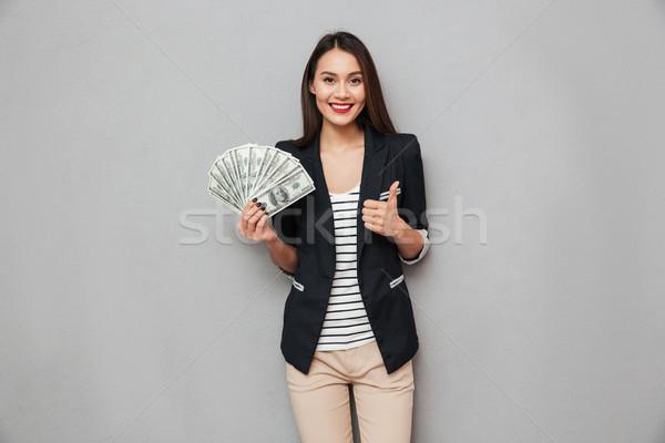 Elégedett ázsiai üzletasszony tart pénz mutat Stock fotó © deandrobot