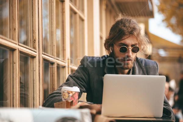 Portré koncentrált szakállas férfi fülhallgató ül Stock fotó © deandrobot