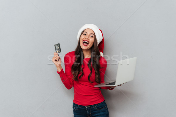 Overjoyed young woman ib Santa's hat holding credit card and lap Stock photo © deandrobot
