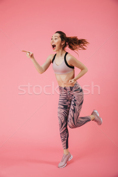 Vertical image of Surprised happy sportswoman running Stock photo © deandrobot