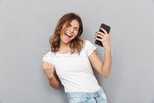 肖像 満足した 若い女性 携帯電話 祝う ストックフォト © deandrobot