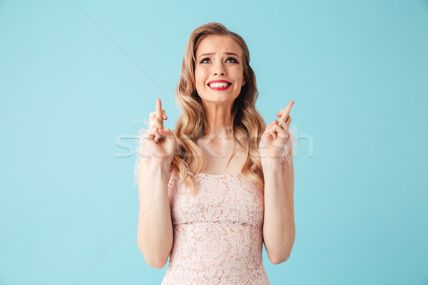 Worried blonde woman in dress praying with crossed fingers Stock photo © deandrobot