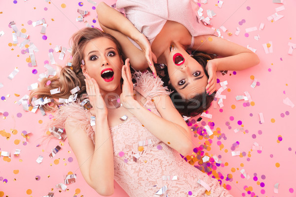 Image of excited women in dresses lying on the floor under falli Stock photo © deandrobot