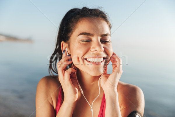 Cheerful sports woman listening music in earphones with closed eyes Stock photo © deandrobot
