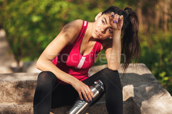 Tired young sportswoman holding water bottle Stock photo © deandrobot