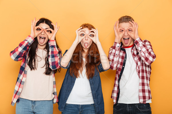 Group of funny school friends grimacing and having fun Stock photo © deandrobot