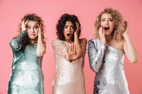 Stock photo: Three beautiful confused women in shiny dresses