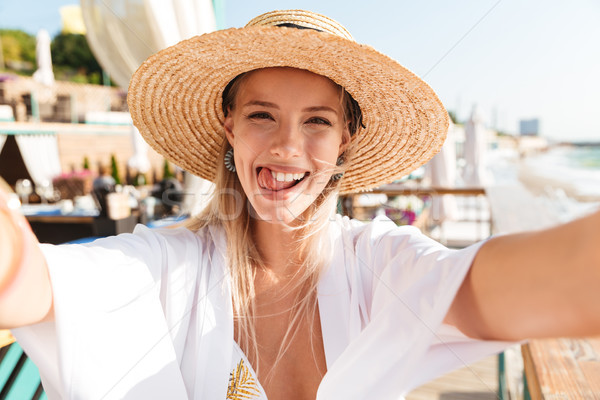 Happy young girl in summer hat and swimwear resting Stock photo © deandrobot