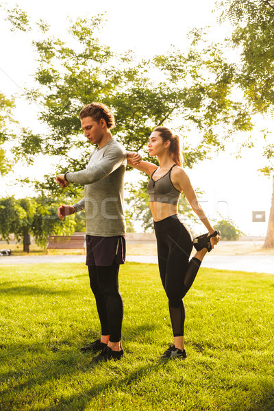Photo of healthy caucasian man and woman 20s in tracksuits, doin Stock photo © deandrobot