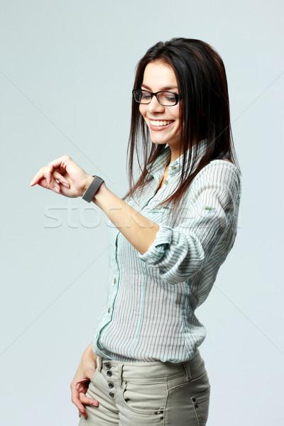 Jonge glimlachend zakenvrouw naar horloge pols Stockfoto © deandrobot