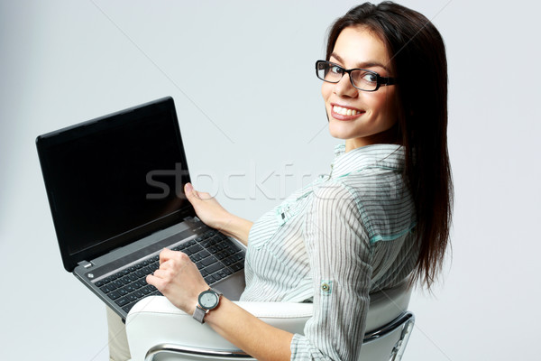 Young smiling businesswoman using laptop and looking at camera on gray background Stock photo © deandrobot