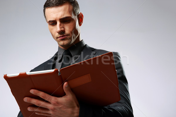 Smart businessman using tablet computer over gray background Stock photo © deandrobot