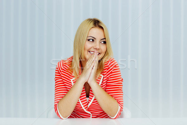 Young smiling woman sitting at the table and looking to the left at copyspace Stock photo © deandrobot