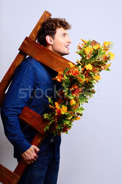 Portrait of a funny man holding stepladder Stock photo © deandrobot