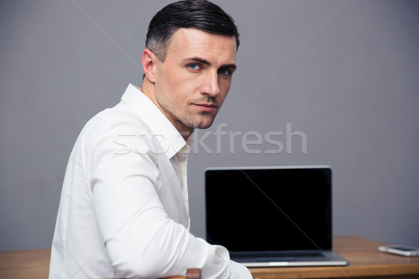 Businessman sitting at thet able with blank laptop screen Stock photo © deandrobot