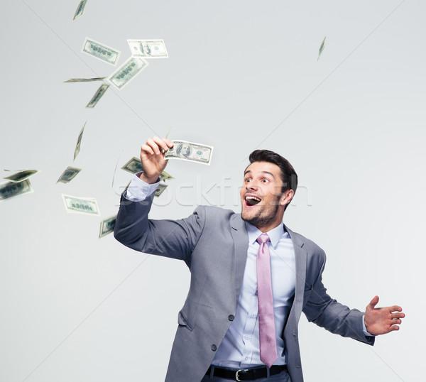 Businessman standing under money rain Stock photo © deandrobot