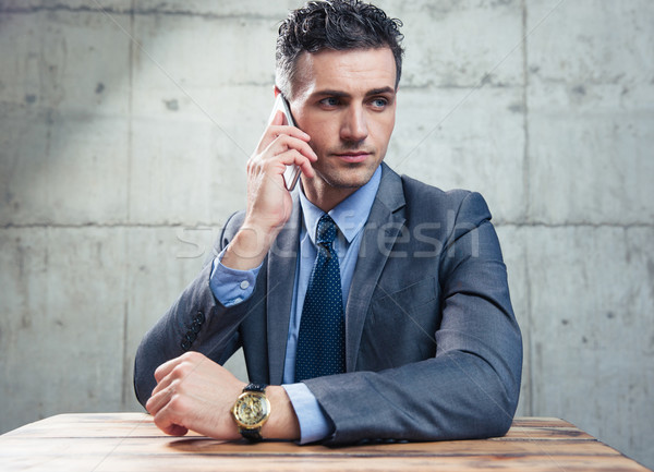 Businessman sitting at the table and talking on the phone Stock photo © deandrobot