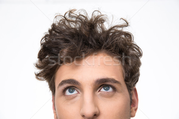 Crop image of a handsome young man with curly hair looking up at copyspace Stock photo © deandrobot