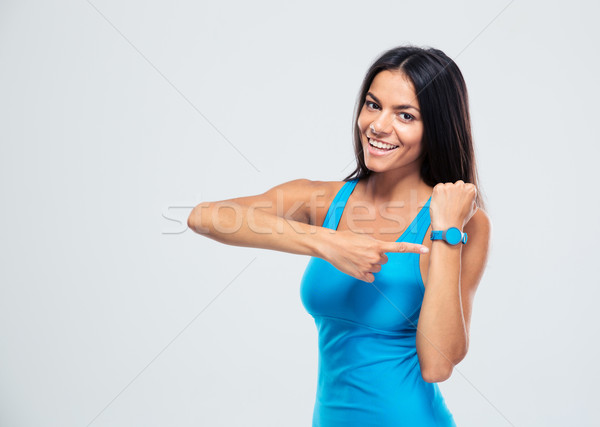 Happy fitness woman pointing on fitness tracker Stock photo © deandrobot