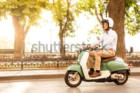 Young happy woman driving vintage scooter in old european town  Stock photo © deandrobot