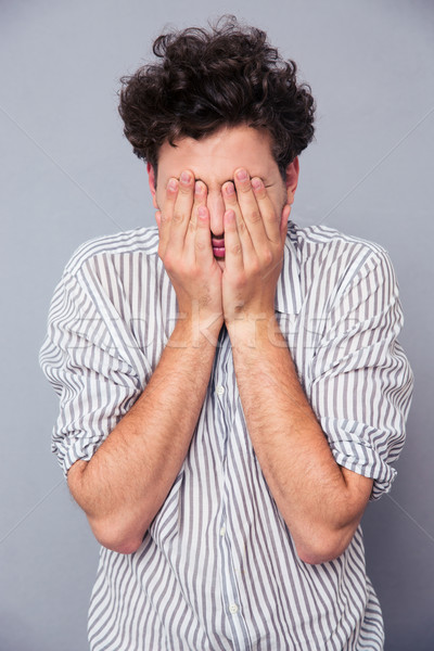 Man covering his face with palms  Stock photo © deandrobot