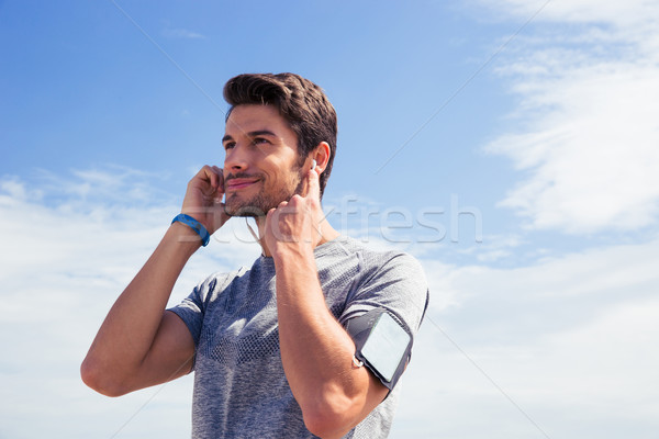 Portrait of a young man in sports wear outdoors Stock photo © deandrobot