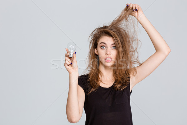 Funny woman holding bulb Stock photo © deandrobot