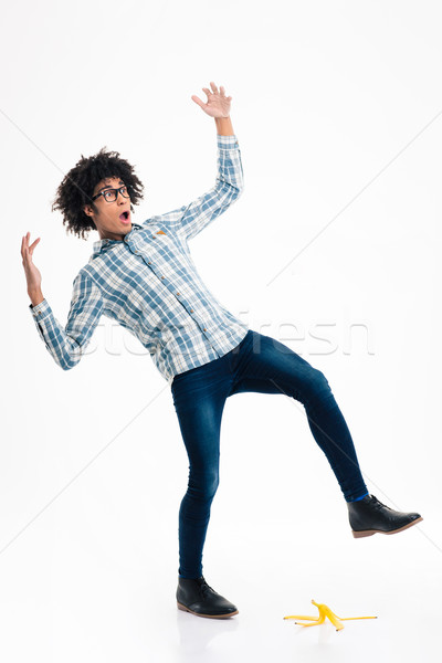 Afro american man slipping on banana skin Stock photo © deandrobot