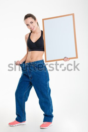 Sportswoman holding blank board and pointing on it  Stock photo © deandrobot