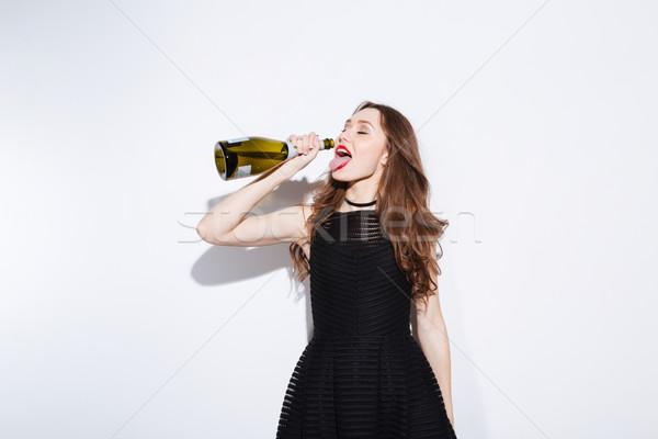 женщину черное платье питьевой шампанского бутылку изолированный Сток-фото © deandrobot