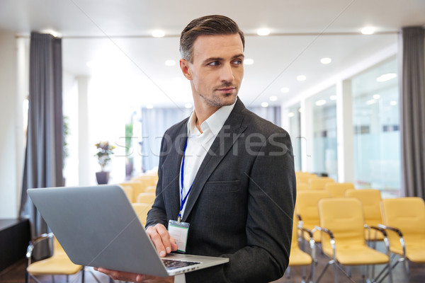 Serious businessman holding laptop in empty meeting hall Stock photo © deandrobot
