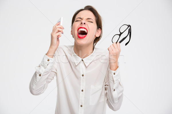 Mad desperate business woman with smartphone and glasses  screaming Stock photo © deandrobot