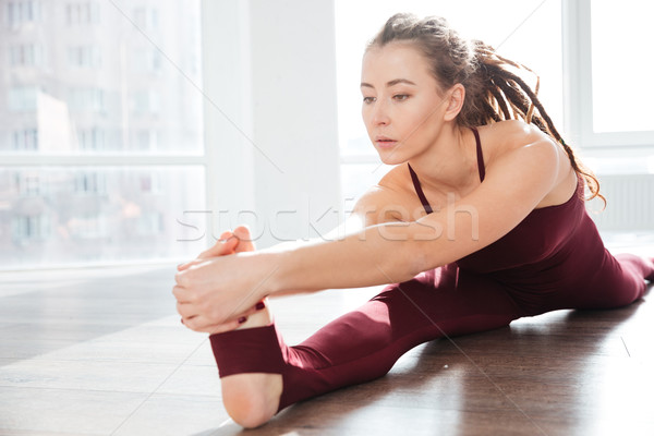 Focused young woman with dreadlocks sitting and stretching legs Stock photo © deandrobot