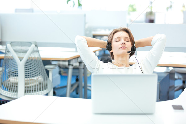 Carefree pretty woman sitting and relaxing on workplace in office Stock photo © deandrobot