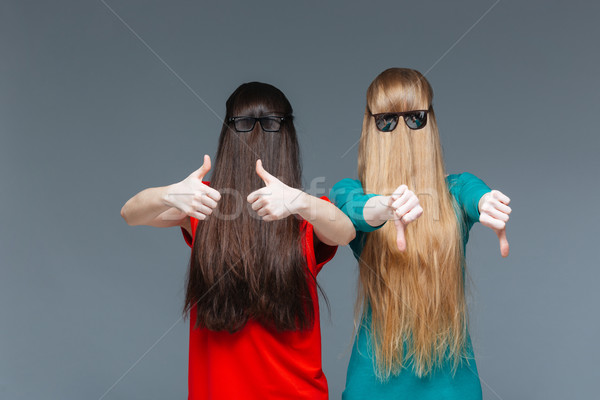 Two comical women with faces covered by long hair gesturing Stock photo © deandrobot