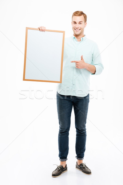 Cheerful man holding blank white board and pointing on it Stock photo © deandrobot