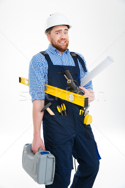 Stock photo: Funny bearded young builder holding tools and blueprints