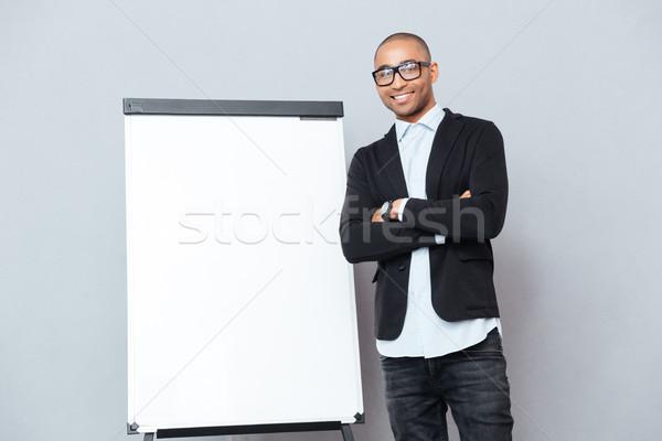 Sorridere african uomo piedi braccia incrociate lavagna a fogli mobili Foto d'archivio © deandrobot