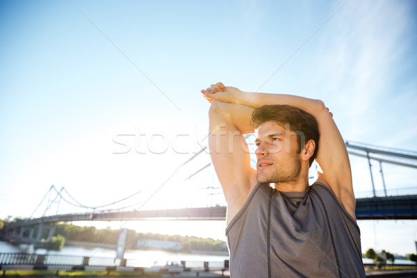 Sports man stretching at the bridge railing and looking away Stock photo © deandrobot