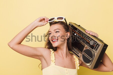 Woman in red swimsuit standing outdoors and holding vintage boombox Stock photo © deandrobot